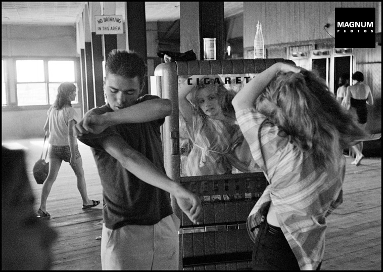 USA. New York City. 1959. Brooklyn Gang. Coney Island. Kathy fixing her hair in a cigarette machine mirror.